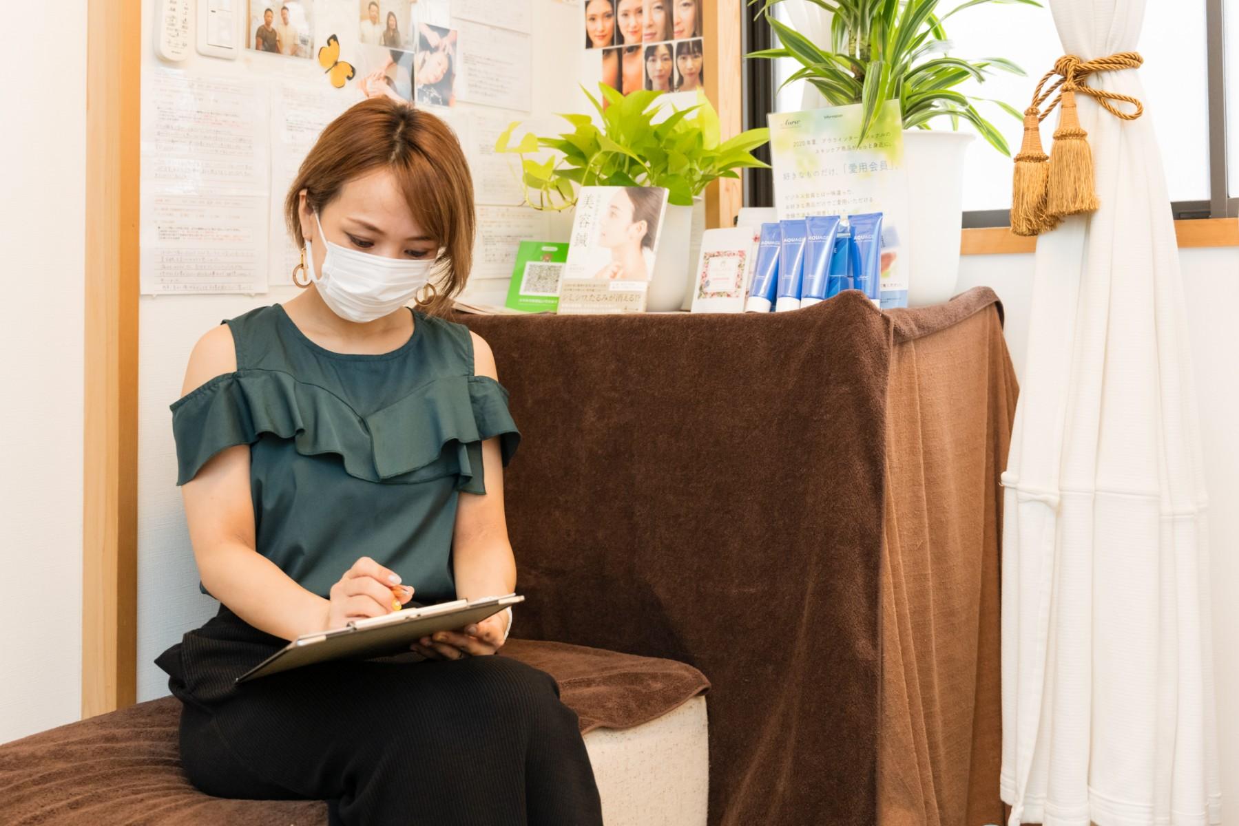北梅田美容鍼灸院の初回施術で問診票を記入している様子